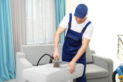 worker removing dirt from furniture in flat