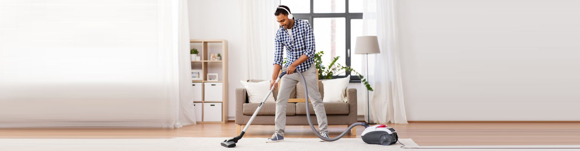 male housekeeping cleaning the carpet using vacuum cleaner